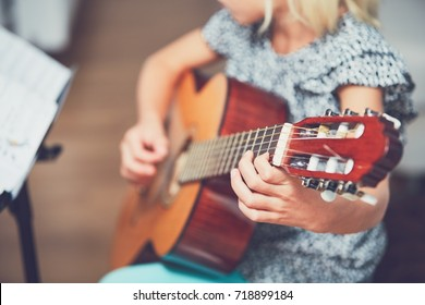 Little girl learning to play to the guitar at the home. Selective focus on the string.
