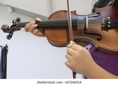 little girl learning to play violin. close-up