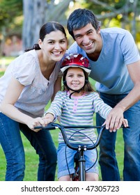 Little girl learning to ride a bike with her parents in a park