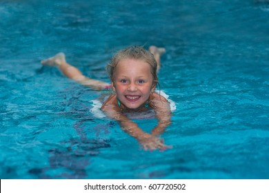 Little girl learning to swim in big sport pool. Swimming school for small children. Healthy kid enjoying active lifestyle. Preschooler practicing with foam pad.