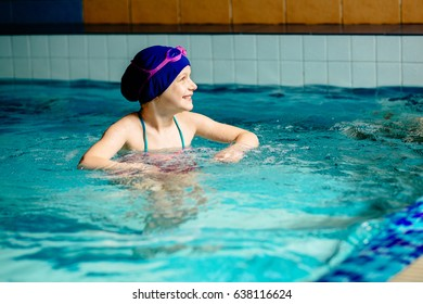 Little girl learning to swim and laughing in big sport pool. Swimming school for small children. Healthy kid enjoying active lifestyle.