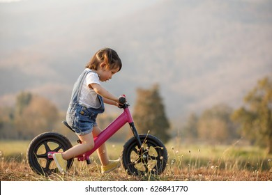 Little girl learns to keep balance while riding a bicycle