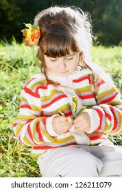 Little Girl with Leaves Outdoors on Autumn Sunny Day