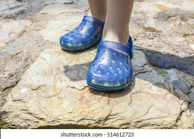 5c949655f221a2 Little girl legs wearing her blue plastic clogs just after swimming