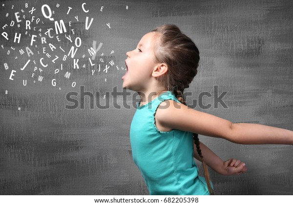 Kleines Mädchen und Briefe auf grauem Hintergrund. Sprachtherapie-Konzept