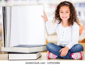 Little girl at the library with a big book