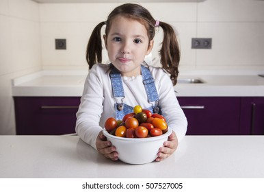Little girl licking her lips  with cherry tomatoes bowl. Education on healthy  nutrition for children