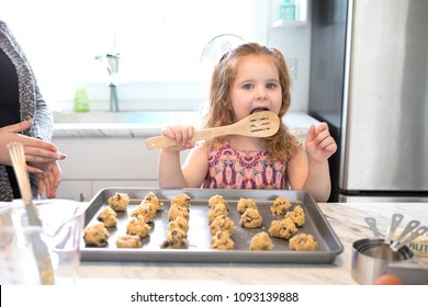 A little girl licking the spoon while baking cookies