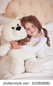 A little girl lies in a bed in a baby's beige room. He hugs a toy of a polar bear. Good morning.