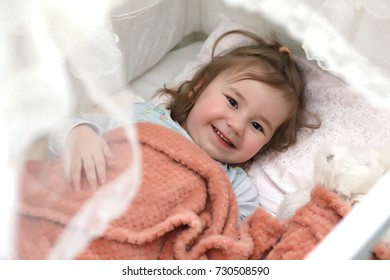 Little girl lies in bed on pillow and smiles
