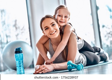 A little girl lies on her mother's back while resting after workout in gym atmosphere with dumbbells, mat, fitness ball, bottle of water on the floor. Healthy family leisure concept