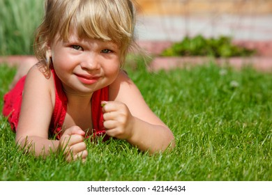 The little girl lies on a lawn