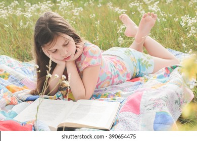 Little girl lies on the patchwork rug on the field, eats a candy and reads a book in the light sunny summer day