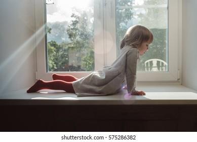 Little girl lies on a windowsill