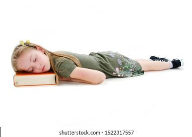 The little girl lies and sleeps on the floor. The child fell asleep while reading a book. Isolated on white background