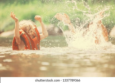 Little girl in a life jacket swimming and splashing in the water