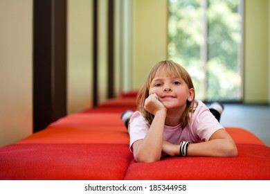 Little girl lifestyle shot in  a sunny room with her hand on her face laying on a red couch with an out of focus background and  room for copy