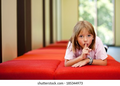 Little girl lifestyle shot in  a sunny room with her finger to her lips asking for quiet or silence laying on a red couch with an out of focus background and  room for copy