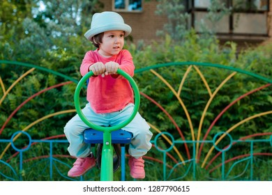 A little girl likes to play on the playground. Children's fun physical development in the open air.