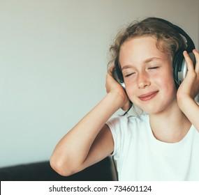 Little girl listening to the music in headphones.