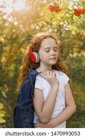 Little girl listening to music on headphones in a summer park.