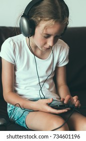 Little girl listening to the music on the phone.