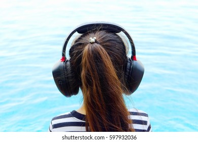 Little girl listening to music at the swimming pool.back view