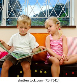 little girl listens to her big brother reading a childrens book at school