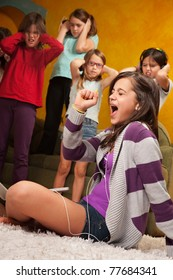 Little girl listens to music on headphones and  sings while friends cover their ears