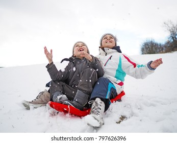 Little girl and littel boy playing in the snow