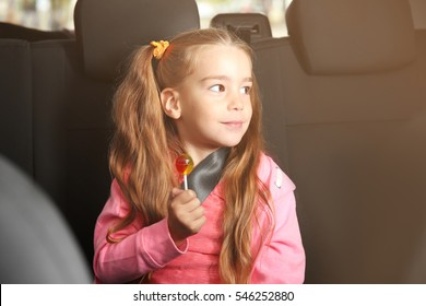 Little girl with lollipop in a car