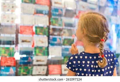 Little girl with lollipop near postcard kiosk.