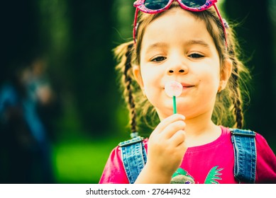 Little girl with lollipop outdoor in the park