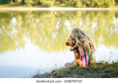 little girl with long blond hair crying and hugging her teddy bear toy