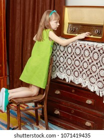 A little girl with long blond hair and a short bangs, in a short summer dress.The girl turns the volume knob on the old radio. Retro style.