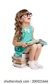little  girl with long curls, in big optical glass sit on pile of old books holding opened book and  look up isolated on white