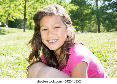 little girl with long hair and cheerful smile outdoor