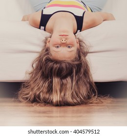 Little girl with long hair lying upside down on sofa at home. Kid playing having fun on couch.