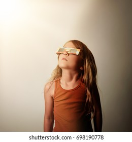 A little girl is looking at the 2017 solar eclipse with protective eye glasses on an isolated background with shadows for a space science concept.