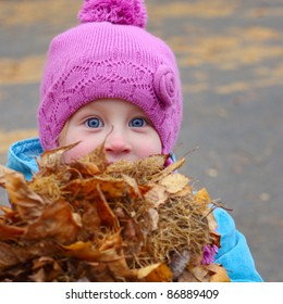 Little girl looking to a camera and holding heap of autumn leaves