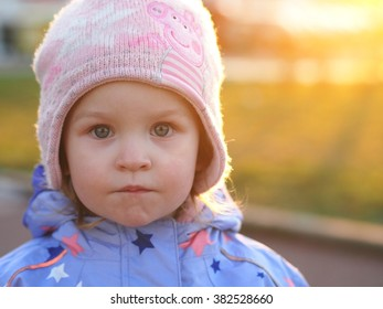 Little girl looking to the camera - serious neutral look. Spring sunlight in the background.