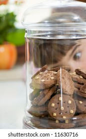 little girl looking at cookies in a jar