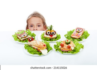 Little girl looking at creative food creatures - craving the party sandwiches, isolated