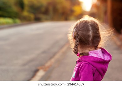Little girl looking to cross the street. Rear view.