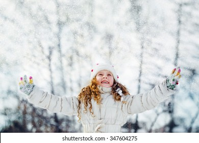 Little girl looking for falling snow. Falling snow around the child. Happy childhood and freedom concept.
