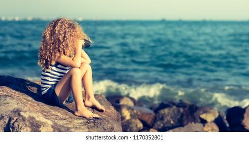 Little girl looking far away with binoculars, sitting on a rock near a sea