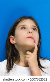 Little girl looking up with finger on mouth thinking of an idea over blue background