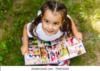 Little girl looking at her album photo