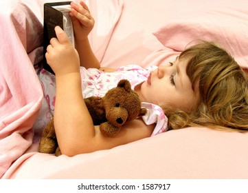 Little girl looking at her Bible before bedtime