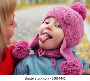 Little girl looking to her mother and making face